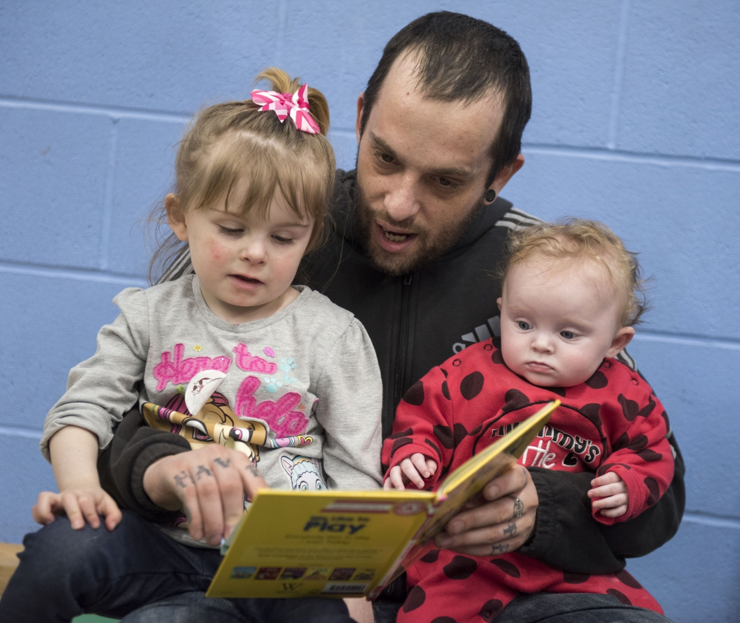 Man reading with two children